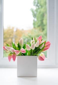窓辺に花のチューリップと正方形の白い花瓶