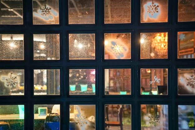 正方形の窓は、タイのバンコクにあるクラブパブとバーの内側と外側の反対側を透けて見えます。