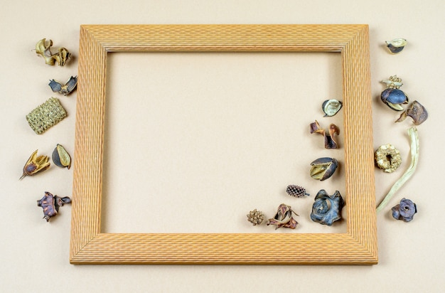 Square wood frame with dry vanilla flowers round on the paper pastel background