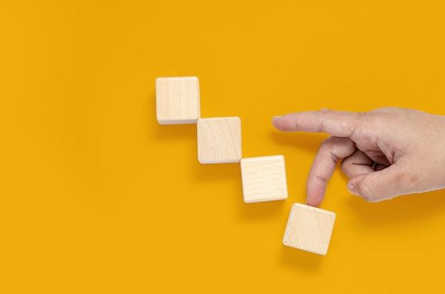 正方形の木製ブロックが黄色の背景に配置され、手が上向きに歩いており、最後のピースが崩壊しているように見えます。ウッドブロックのコンセプト、テキスト、ポスター、モックアップテンプレートのコピースペースのバナー。