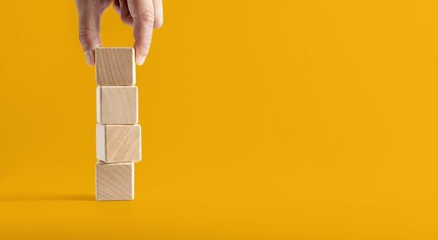 正方形の木製ブロックが黄色の背景に互いに積み重ねられ、上部の木製ブロックを持ち上げて続行します。テキスト、ポスター、モックアップテンプレートのコピースペースと木製ブロックコンセプトバナー。
