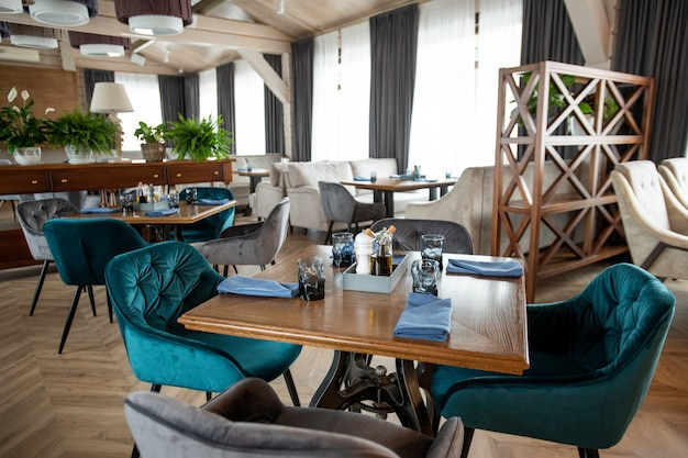 아늑한 레스토랑의 대형 홀 중앙에 4 개의 편안하고 부드러운 안락 의자가 서있는 고객을위한 정사각형 나무 테이블 제공