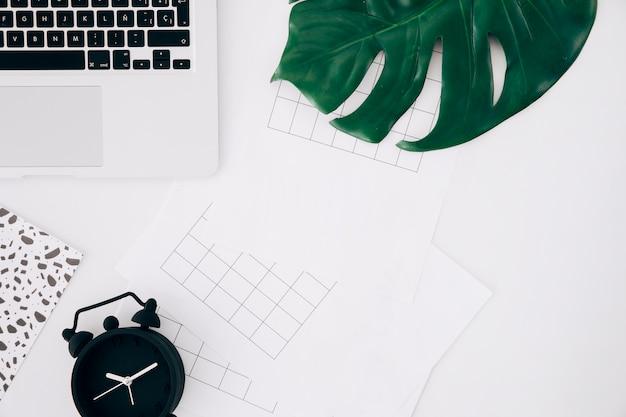 Squared paper sheet; alarm clock; monster leaf and laptop on white desk