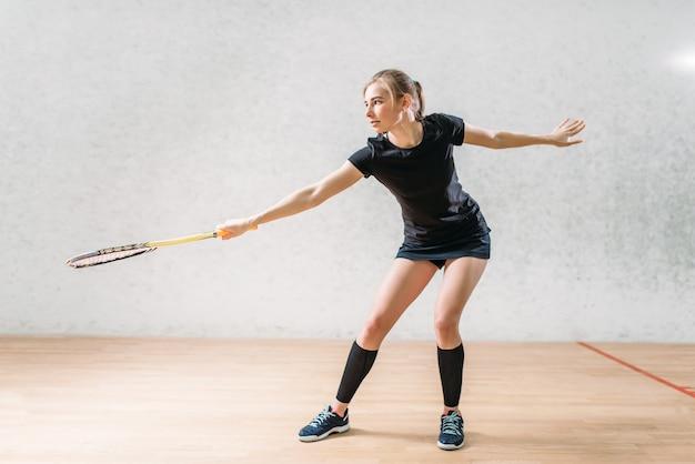 Обучение игре в сквош, игрок женского пола с ракеткой в руках,