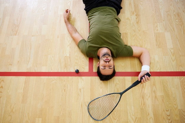 Игрок в сквош на полу
