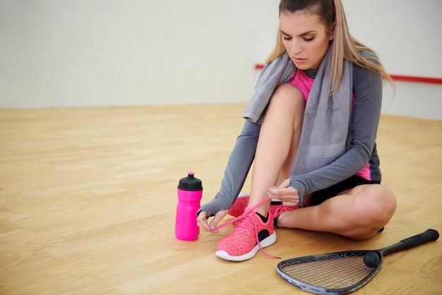 Игрок в сквош, связывающий спортивную обувь