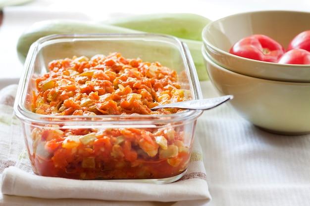 四角いガラス皿にニンジンとトマトを入れたスカッシュシチュー