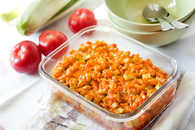Squash stew with carrot and tomatoes in a square glass dish