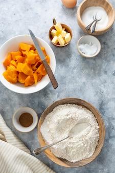 スカッシュタルト。パンプキンパイを調理するための材料。秋のデザート。パン屋の背景