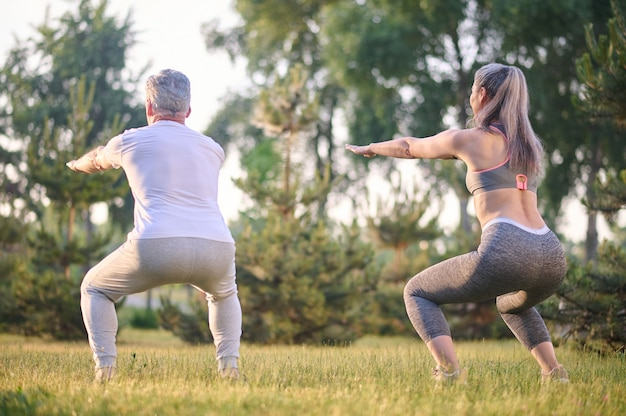 Squats . a man and a woman squating during exercising in the park