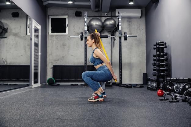 Приседания с корректирующей штангой. вид сбоку на привлекательную стройную женщину в спортивной одежде, которая в хорошей форме делает приседания со штангой для устойчивости. выпрямление и правильная осанка, гибкость мышц и спорт