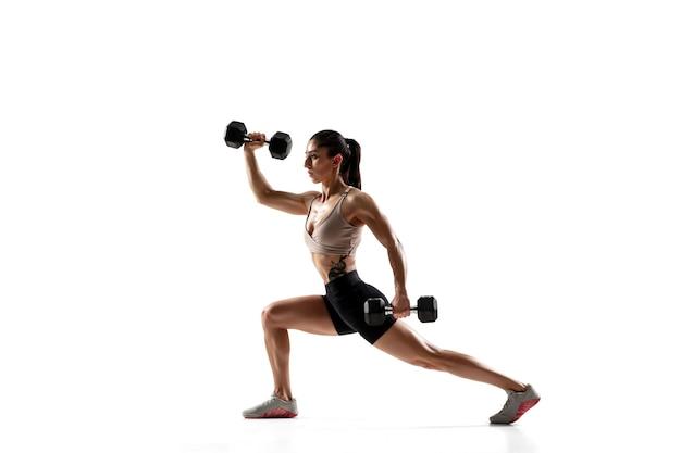 重みのあるスクワット。白い壁に分離された白人のプロの女性アスリート トレーニング。筋肉質でスポーティーな女性。アクション、モーション、若さ、健康的なライフスタイルのコンセプト。広告用の copyspace。