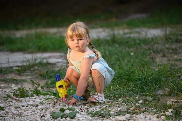 Сидящая на корточках маленькая блондинка с водяным пистолетом играет секретного агента