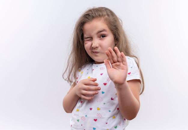 격리 된 흰색 배경에 중지 제스처를 보여주는 흰색 티셔츠를 입고 squeamish 작은 학교 소녀