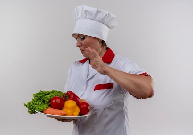 Cuoco femminile di mezza età schizzinoso in uniforme del cuoco unico che tiene le verdure sulla zolla