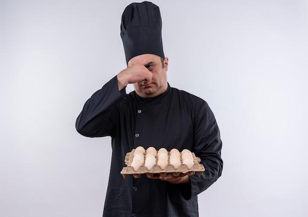 Cuoco maschio di mezza età schizzinoso in uniforme del cuoco unico che tiene lotto di uova chiuse il naso
