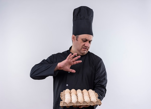 Cuoco maschio di mezza età schizzinoso in uniforme del cuoco unico che tiene lotto delle uova