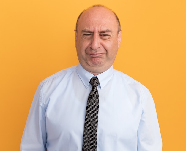 Squeamish middle-aged man wearing white t-shirt with tie isolated on orange wall