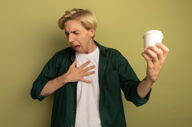 Squeamish with closed eyes young blonde guy wearing green t-shirt holding cup of coffee and putting hand on chest