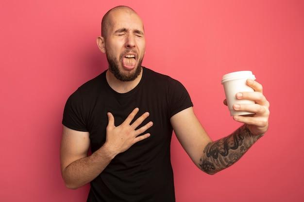 目を閉じてきしむ若いハンサムな男は、胸に手を置いてコーヒーのカップを保持しています