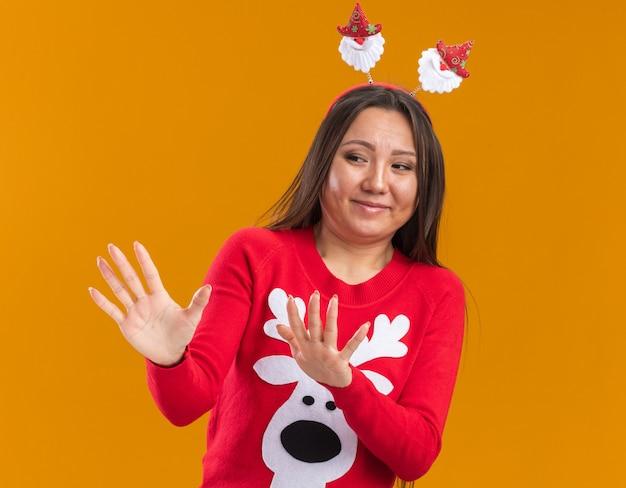 Брезгливая молодая азиатская девушка в рождественском обруче для волос со свитером, протягивающим руки сбоку, изолированным на оранжевой стене