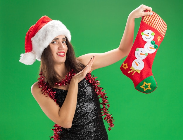 Squeamish young beautiful girl wearing christmas hat with garland on neck holding christmas sock isolated on green background
