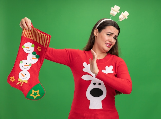 Squeamish young beautiful girl wearing christmas sweater with christmas hair hoop holding christmas socks showing stop gesture isolated on green background