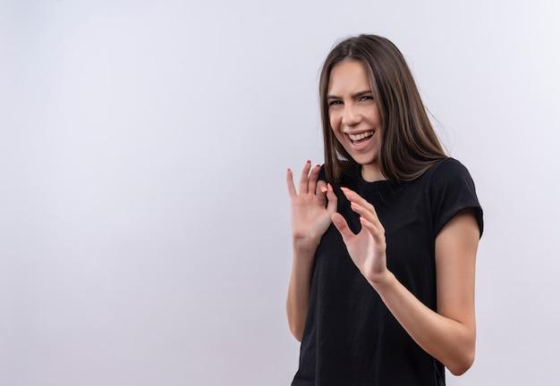 Squeamish giovane ragazza caucasica che indossa la maglietta nera su sfondo bianco isolato