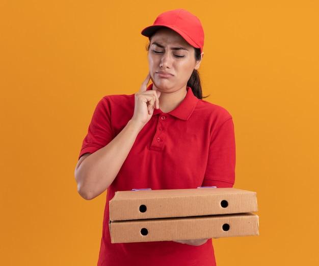오렌지 벽에 고립 된 뺨에 손가락을 넣어 피자 상자를 들고 유니폼과 모자를 쓰고 끽끽 거리는 젊은 배달 소녀