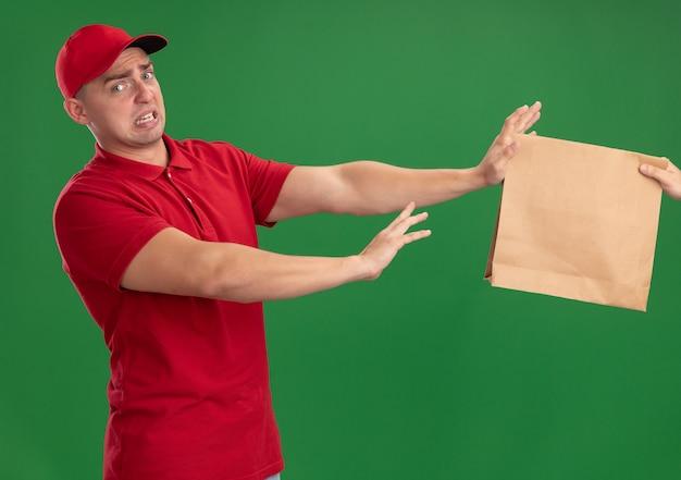 Giovane fattorino schizzinoso che indossa l'uniforme e il cappuccio che dà il pacchetto di cibo di carta al cliente isolato sulla parete verde