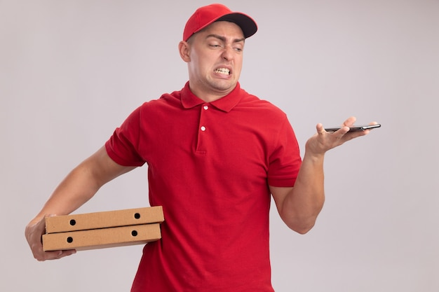 피자 상자를 들고 흰 벽에 고립 된 그의 손에 전화를보고 모자와 유니폼을 입고 squeamish 젊은 배달 남자