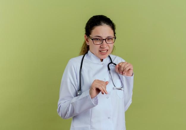 Giovane medico femminile schizzinoso che indossa veste medica e stetoscopio con gli occhiali isolati sulla parete verde oliva