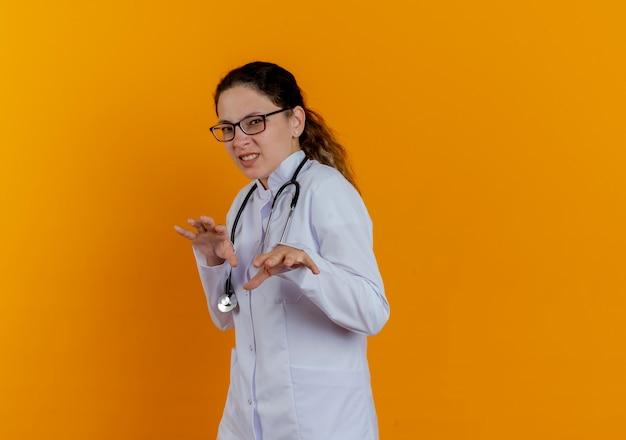 Giovane medico femminile schizzinoso che indossa veste medica e stetoscopio con gli occhiali isolati