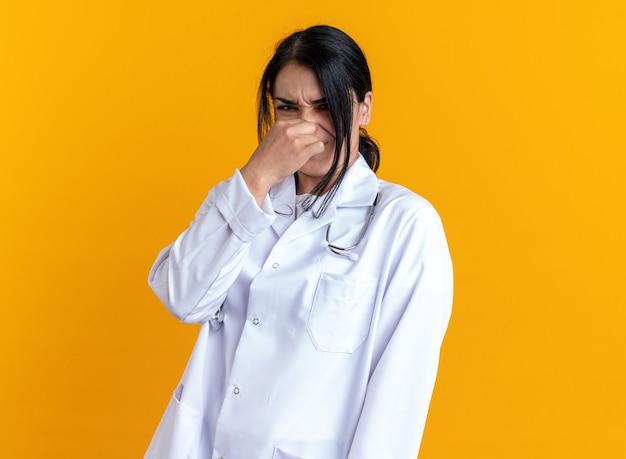 Giovane dottoressa schizzinosa che indossa una tunica medica con uno stetoscopio chiuso il naso isolato su sfondo giallo