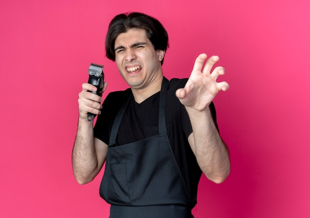 머리 가위를 잡고 분홍색에 고립 된 호랑이 스타일 제스처를 보여주는 제복을 입은 젊은 잘 생긴 남성 이발사