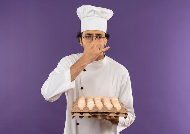 Брезгливый молодой мужчина-повар в униформе шеф-повара и в очках держит партию яиц и закрывает нос на фиолетовом
