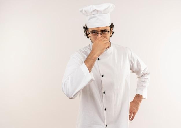 Giovane cuoco maschio schizzinoso che indossa l'uniforme dello chef e gli occhiali chiusi il naso e mettendo la mano sull'anca isolata sul muro bianco