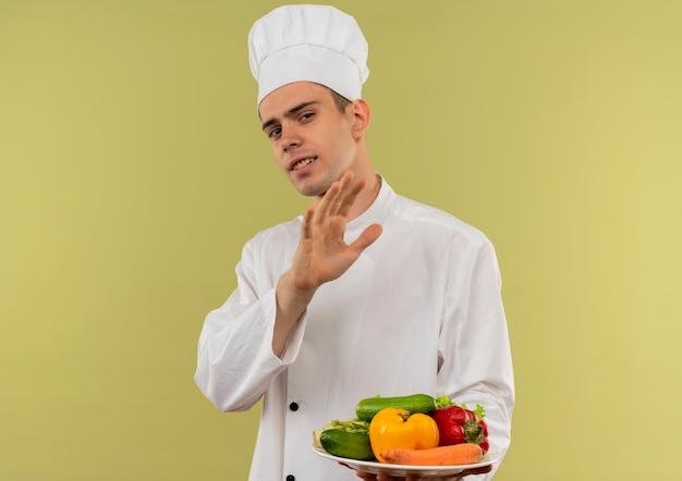 Cucinare maschio giovane schizzinoso che indossa le verdure della tenuta dell'uniforme del cuoco unico sulla zolla che mostra il gesto di arresto con lo spazio della copia