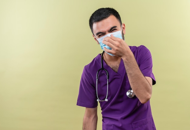 Schizzinoso giovane medico maschio indossa viola chirurgo abbigliamento e stetoscopio maschera medica naso chiuso su sfondo verde isolato