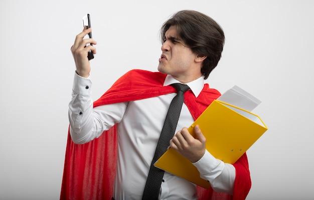 Брезгливый молодой супергерой в галстуке держит папку и смотрит на телефон в руке, изолированной на белом фоне