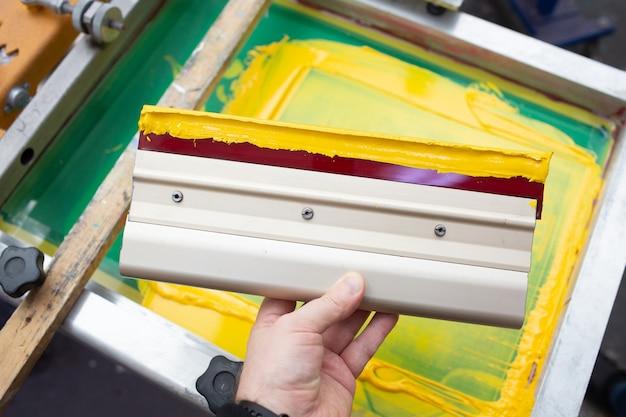 縫製工場でのシルクスクリーン印刷工程用スキージ フレームスキージとプラスチゾルカラー塗料