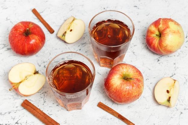 白いコンクリートの背景にシナモンとスライスしたリンゴとガラスの絞りリンゴジュース