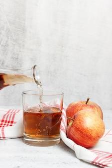 絞りたてのリンゴジュースをタオルでグラスに注いでいます