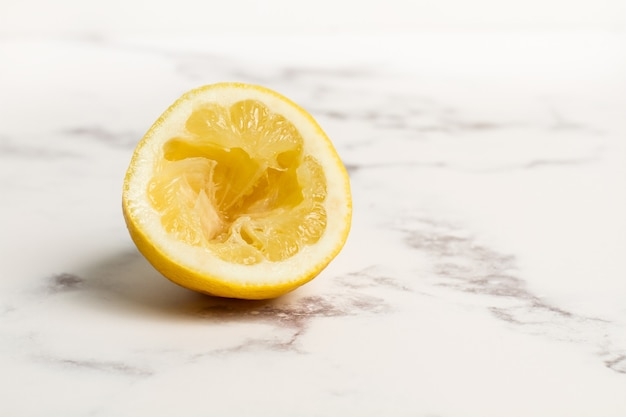 Squeezed half lemon on marble table