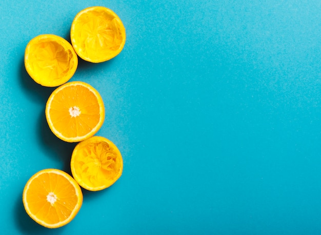 Squeezed oranges on blue background