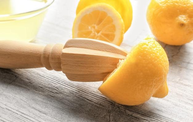 Соковыжималка и лимоны на деревянном столе