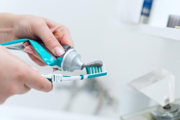 Выжимает зубную пасту на зубной щетке в размытом интерьере ванной комнаты. утреннее время, личная гигиена полости рта