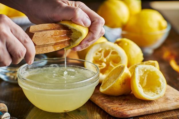 Выдавливание свежего лимонного сока с деревянной пастой в миску