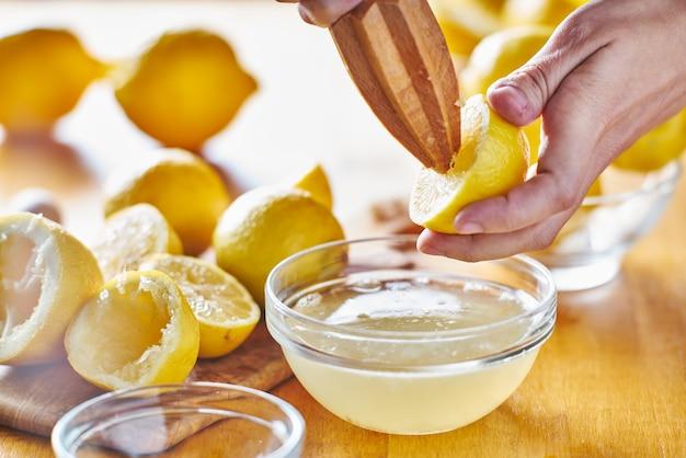 ボウルに木製リーマで新鮮なレモンジュースを絞る