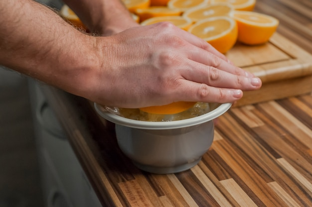 Squeezing oranges to make a fresh and natural juice. closeup on man making fresh orange juice. oranges and juicer on the wooden cutting board